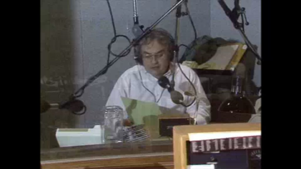 Dale Goldhawk reading an announcement into the radio mic