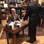 Author Gene Allen signs copies of his book Making National News